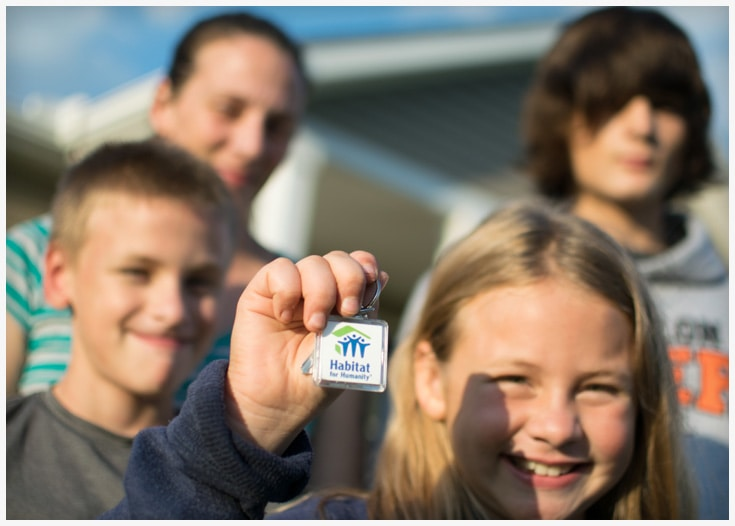 Habitat for Humanity family with keys in front of their house