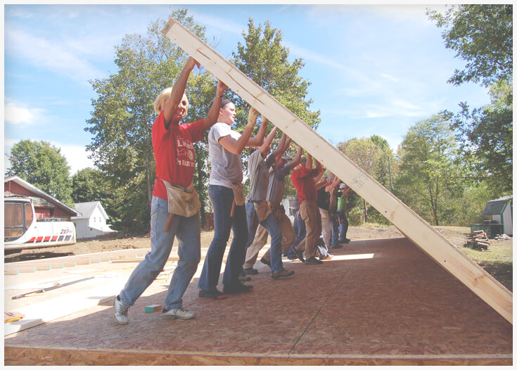 Volunteers raising the wall of a decent, affordable home