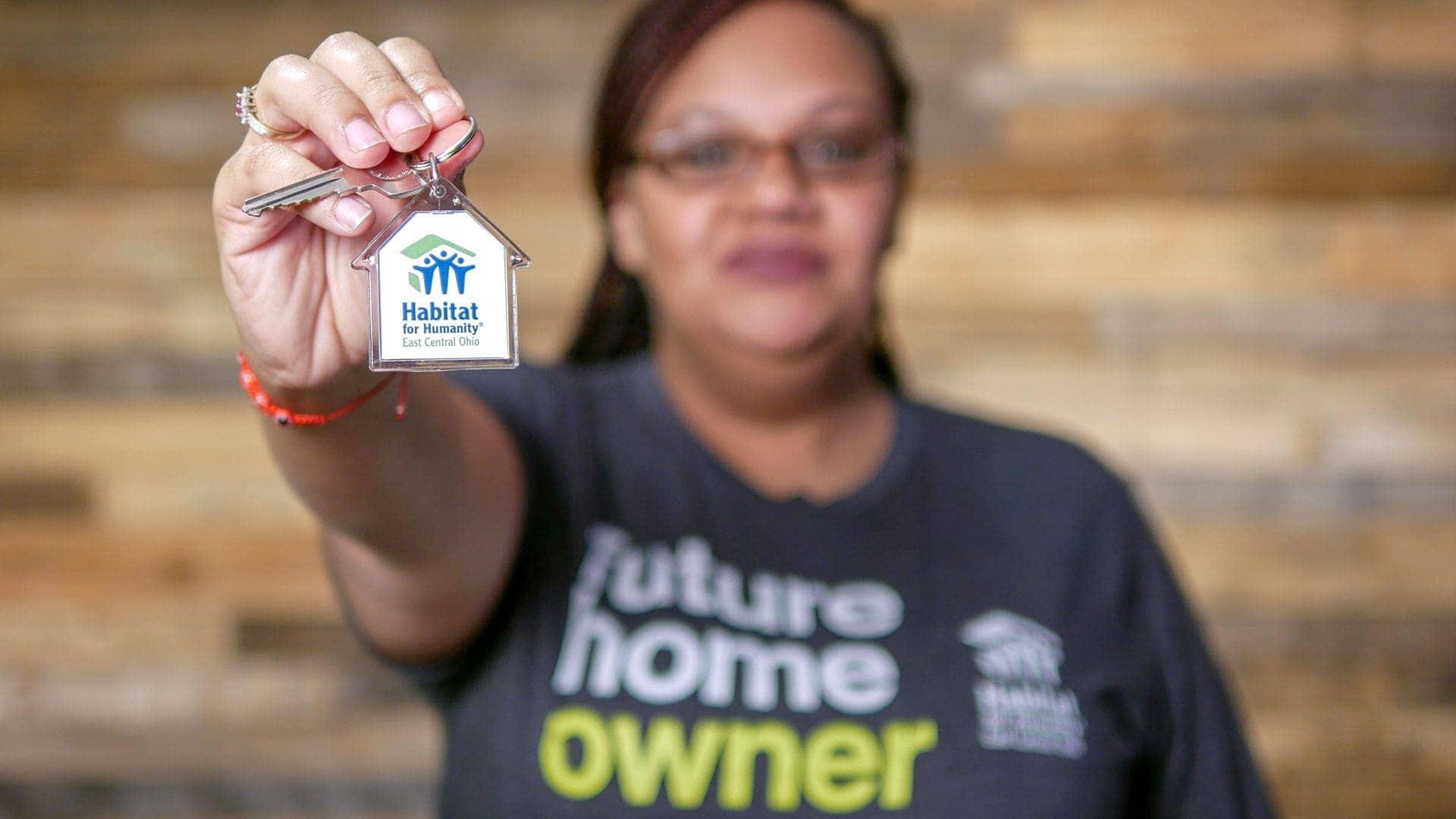 Habitat for Humanity homeowner holding keys to home.